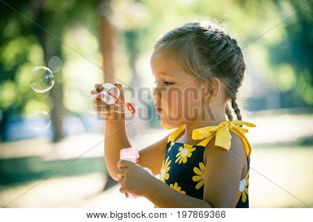 cute little girl play in park blow soap bubbles profile close up summer day