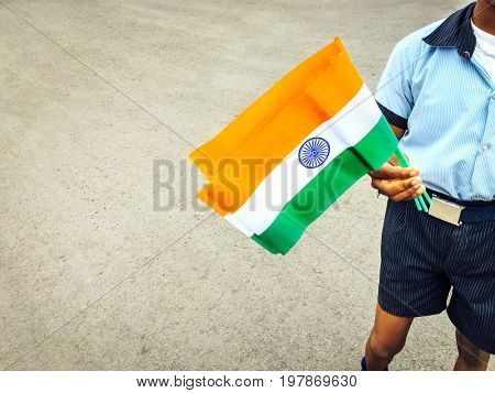 A young boy selling paper flags on the street on the occasion of Indian Independence Day. A partial close up.