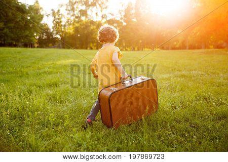 Curvy haired blonde kid wearing orange shirt carrying brown suitcase walking on grass.