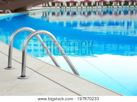 Modern swimming pool with ladder in luxury hotel