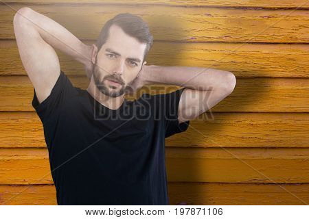 Portrait of man with hands behind head against full frame shot of orange wall