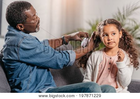 African American Man Combing Daughter