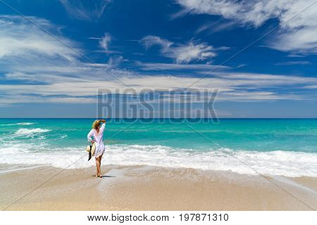 Young woman standing on a beach and enjoying the sun in Greece