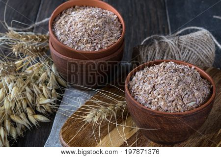 Wheat, Oat bran in clay  bowl and ears of wheat and oat.  Dietary supplement to improve digestion. On dark wooden background