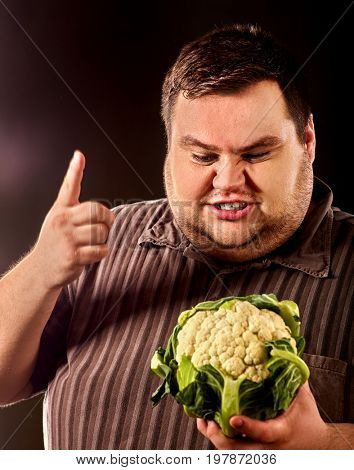 Diet fat man eating healthy food. Healthy breakfast with vegetables cauliflower for overweight person. He is trying to go on a diet. Male trying to lose weight. Concept on black background.