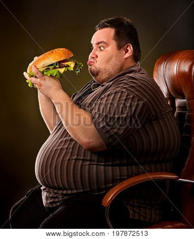 Diet failure of fat man eating fast food hamberger. Happy smile overweight person who spoiled healthy food by eating huge hamburger on fork. Obesity due to eating bad foods. Very fat man eating fast
