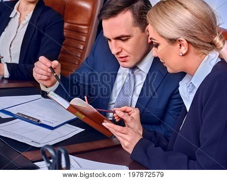 Business people office life of team people working with papers sitting table. Cabinets with folders background. Two young women in suits discuss an economic project. Calculation of expenses for year.