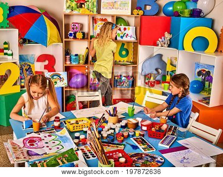 Kids playroom organization of children painting and drawing in kid's club. Craft lesson in primary school. Kindergarten teacher and students work together. Preparation for an art exhibition.