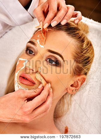 Collagen face mask. Facial skin treatment. Woman receiving cosmetic procedure in beauty salon. Bottle with moisturizing cream on background. Cropped shot of removing wrinkles Mask against sagging skin