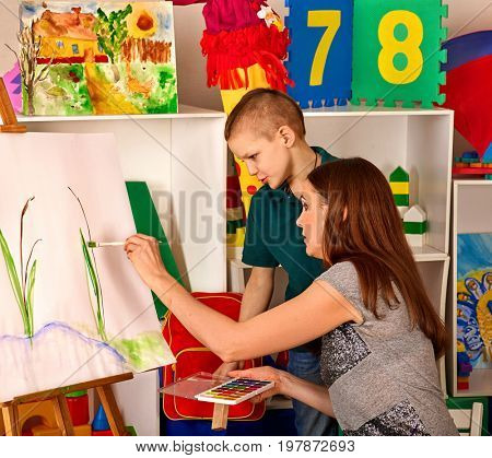 Child painting on easel. Kid boy learn paint by brush in class school. Kindergarten interior on background. Teacher helps the child prepare for the art exhibition.