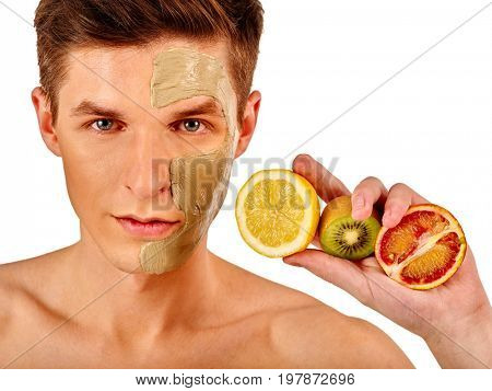 Facial mask from fresh fruits and clay for man concept. Face with treatment mud applied. Male holding lemon half for skin care procedure in salon. Therapeutic mud for the face.