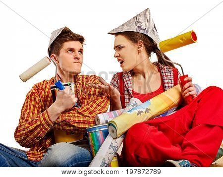 Repair family by happy couple building home. Mad woman and man in newspaper cap renovation apartment by painting tools. They can not repay a loan for repairs.