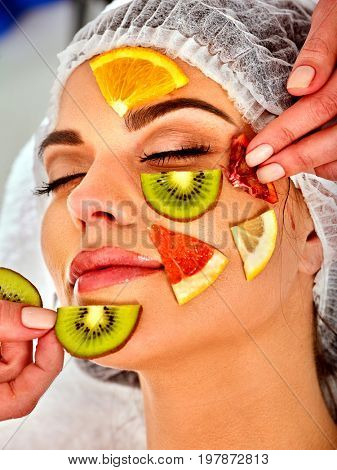 Facial mask from fresh fruits for woman. Beautician apply slices of avocado, grapefruit and kiwi. Girl in medical hat lying on spa bed for skin care procedure in salon. Mask against sagging skin.
