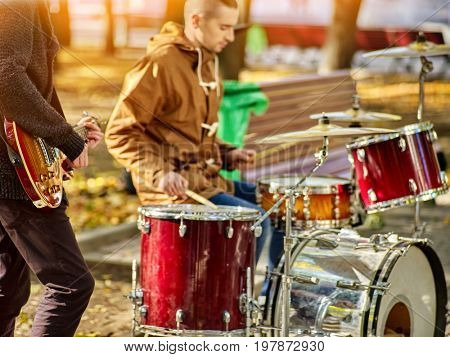 Festival music band. Hands playing on percussion instruments in city park. Drums with sticks closeup. Body part of male musicians. Sharpen is guitar and man hand. People earn money to live.