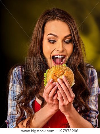Woman eating french hamburger. Portrait of student consume fast food on table. Girl trying to eat junk. Advertise fast food on daek background. Student eats semi-finished products.