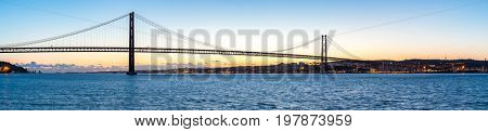 Lisbon cityscape with 25 de Abril suspension Bridge, Portugal at dusk Panorama