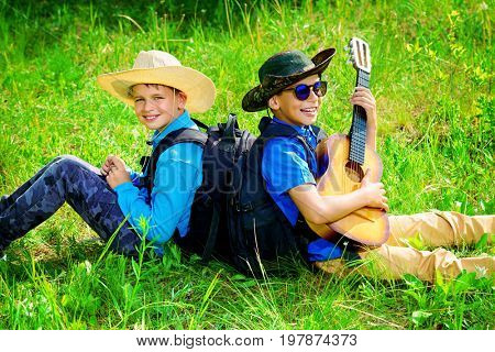Two boys friends go hiking with a guitar and a backpacks. Sunny summer holidays. Outdoor activities.