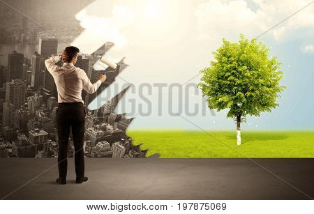Businessman in elegant suit standing with his back, holding a roller and transforming the grey city landscape into green tree in bright nature environment concept