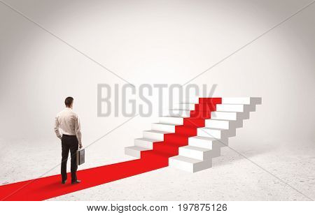 A successful businessman with briefcase standing on red carpet in front of steps in white space concept