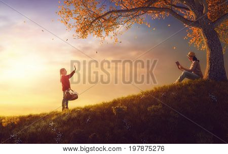 Family picnicking together. Young mother and her child daughter girl enjoying useful outdoor walk sitting on grass in autumn park.