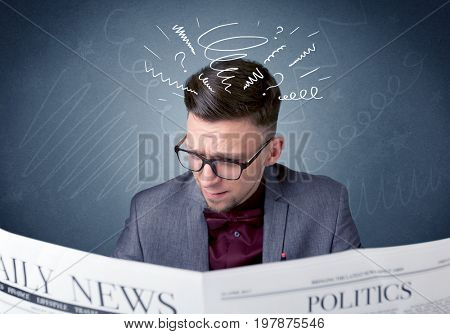 Confused businessman holding newspaper