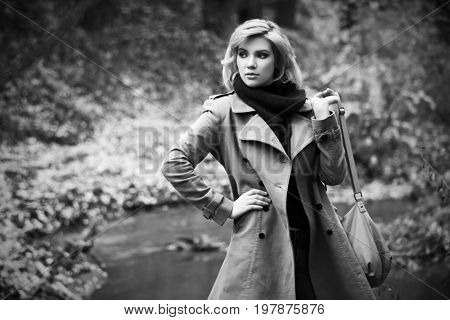 Young fashion blond woman walking in autumn forest. Stylish female model in classic coat with handbag outdoor