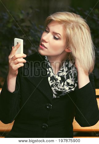 Young fashion blond woman using smart phone on the bench in city street. Stylish female model in black coat outdoor