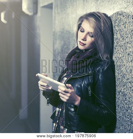 Young woman using tablet computer at the wall. Stylish fashion model in black leather jacket
