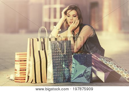 Happy young fashion woman with shopping bags sitting on city sidewalk