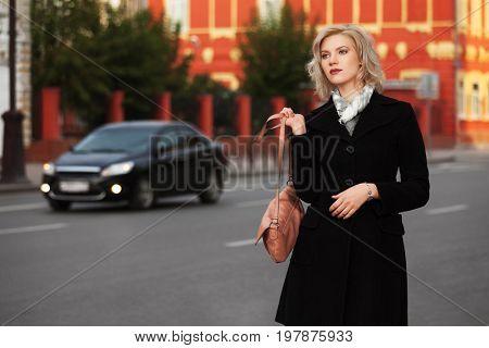 Fashion blond woman in black coat walking in city street. Stylish female model with beige handbag outdoor