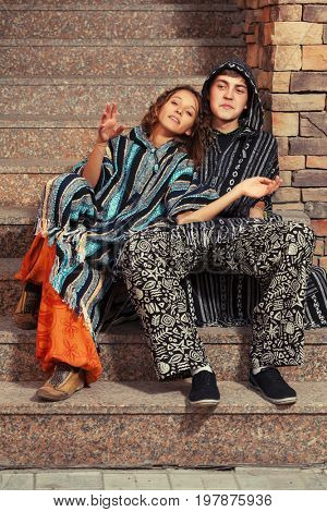 Young fashion hippie couple sitting on the steps. Stylish trendy male and female models outdoor
