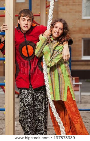 Happy young fashion hippie couple on the playground. Stylish trendy male and female models in hoodie jacket outdoor