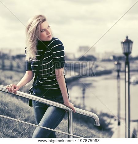 Happy young fashion woman leaning on handrail. Stylish female model in t-shirt and blue jeans outdoor