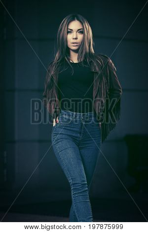 Happy young fashion woman walking in city street. Stylish female model in leather fringe suede jacket and blue jeans