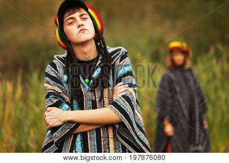 Young fashion hipster couple walking on nature. Stylish trendy male and female model in rasta hat and poncho outdoor