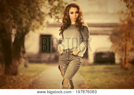 Happy young woman in ripped jeans walking in city street. Stylish fashion model with long curly hairs outdoor