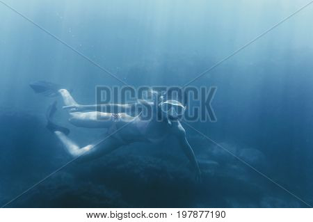 Girl free diving in deep blue sea wearing in mask and snorkel among reef.