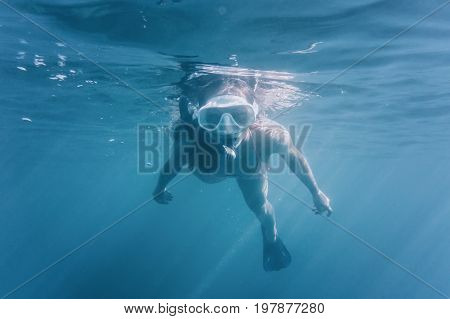 Young woman wearing in mask with snorkel swimming underwater surface among sunbeams.