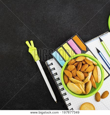 School lunch in a green round container with cookies and almonds on a dark background with handles and notebooks, pencils. Top View.
