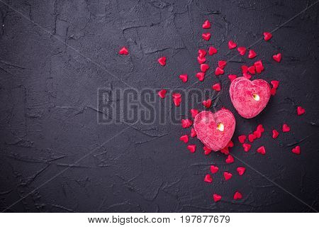 Candles in form of hearts on black slate background. Flat lay.Top view. St. Valentine day background. Place for text.