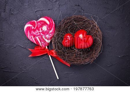 Hearts in nest and lollipop candy on black slate background. Flat lay.Top view. St. Valentine day background.