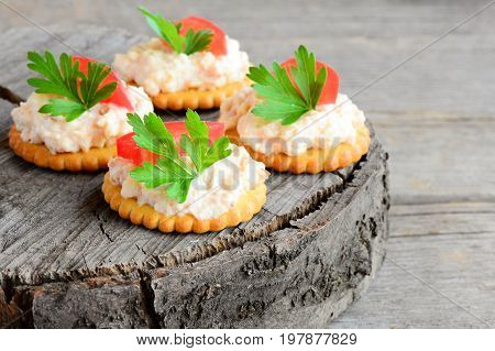Canape cooked from crackers with spicy soft cheese, tomato slice and parsley leaf. Spicy cheese canape on a vintage wooden background. Quick appetizer recipe