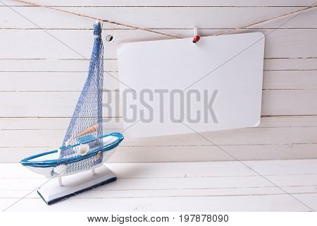 Decorative sailing boat and empty tag on clothes line on wooden background. Selective focus. Place for text.