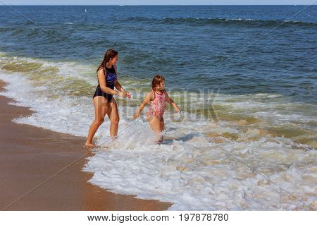 Two sisters swim in the ocean on waves Two cute sisters hugging in the ocean water on a sunny day