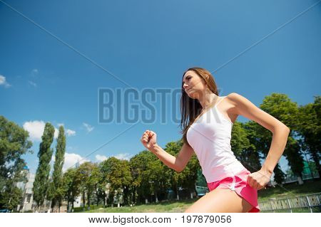 Woman running on arena track. Girl sunny outdoor on blue sky. Coach or trainer at workout. Runner on competition and future success. Sport and healthy fitness.