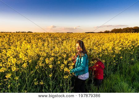 Teenage girl with long hair in yellow bittercress field sunset time