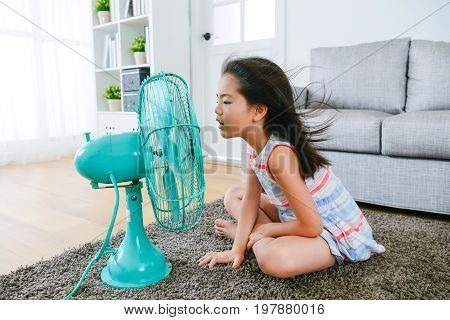 lovely youth little girl sitting on living room floor playing electric fan and enjoying cool wind in summer season at home.