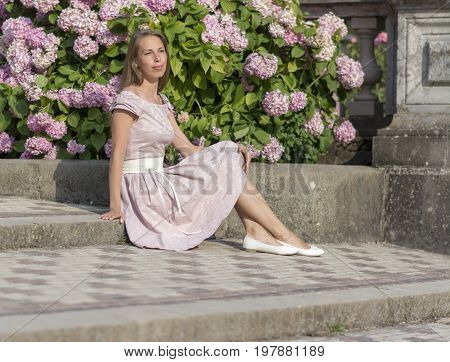 Portrait of a beautiful woman in pink dress sits on a stone staircase on a background of flowers. Stock photo