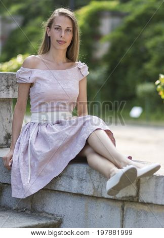 Portrait of pretty white girl in pink dress sitting on the old stone staircase. Stock photo