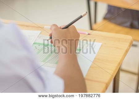 Students concentration holding pencils in hand doing multiple-choice quizzes testing exams answer sheets exercises in school Tests is concept assessment intended to measure knowledge skill aptitude